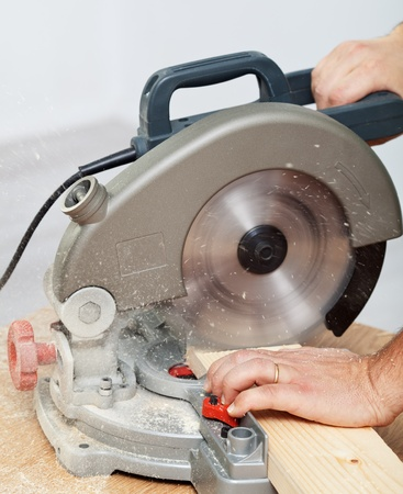 Worker hands cutting wooden plank with electric circular saw - closeup photo