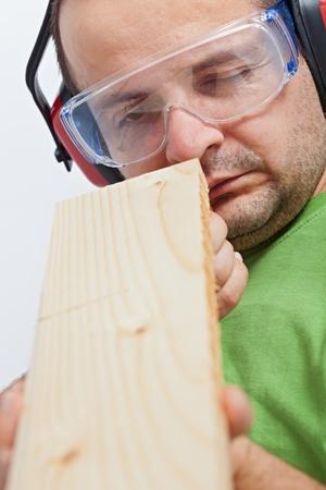 planck: Woodwork - man checking linearity of wooden planck - closeup