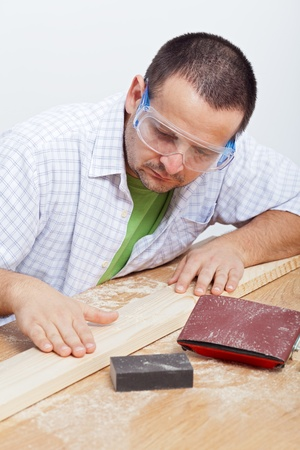 Man polishing wooden planck - checking results on workbench photo
