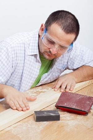planck: Man polishing wooden planck - checking results on workbench