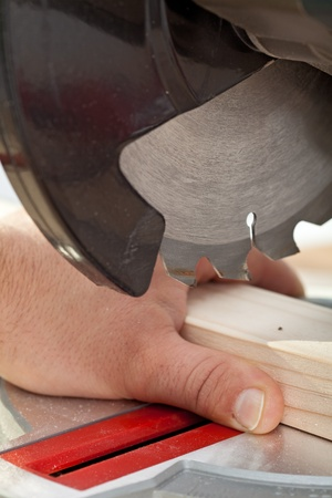 Labor safety concept with circular saw about to cut man finger photo