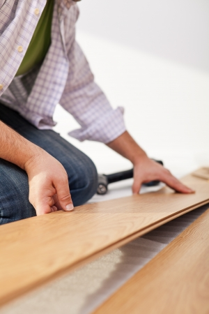 Man laying laminate flooring - closeup on fitting the next piece 免版税图像