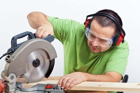 Carpenter cutting wooden plank with circular saw wearing safety equipment photo