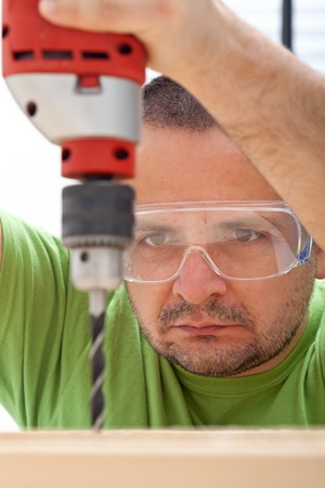 Man drilling wood with power tool - closeup photo
