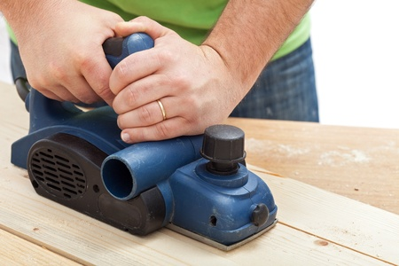 Construction worker hands and power tool - planing a piece of wood Stock Photo - 12375584