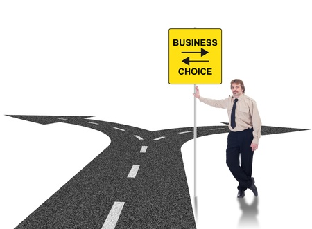 Tough business choices concept with crossroads and businessman leaning on road sign photo