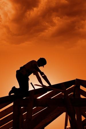 constructeur: Coucher de soleil orageux sur le site de construction avec charpentier de travail Banque d'images