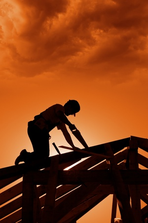 Stormy sunset on construction site with carpenter working photo