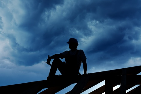 Builder resting on top of roof structure - silhouette against stormy sky 免版税图像