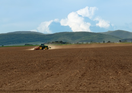 Tractor working the wide field till dusk - large scale agriculture photo