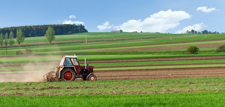 Small tractor harrow on the spring striped field - small scale agriculture photo