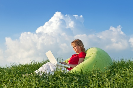 Woman with laptop computer outdoors in the fresh spring grass Stock Photo