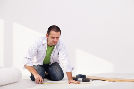 kneeling man: Man laying flooring at home - the isolation layer