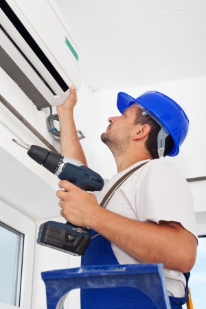 repairmen: Worker installing air conditioning unit - closeup