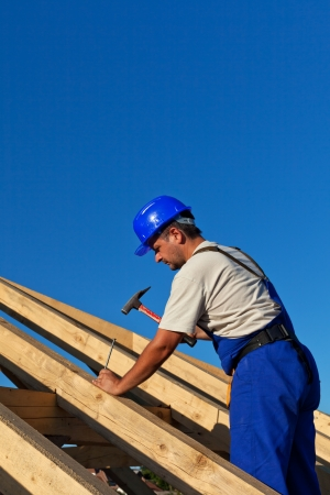 Carpenter building roof structure - driving in large nail photo