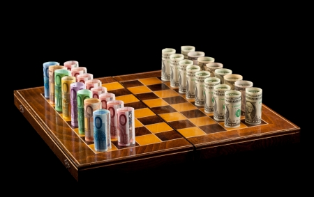 Currency rivalry concept with rolled banknotes on chessboard - isolated photo