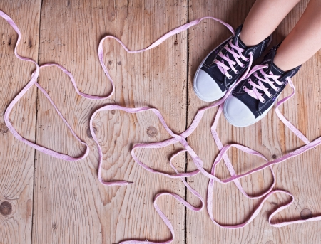 The shoe tie puzzle - child feet and long twisted shoelaces on wooden floor