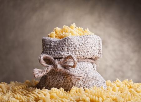 raw gold: Fusilli pasta in burlap bag - traditional healthy food