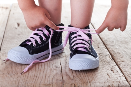 old shoes: Child successfully ties shoes - closeup on feet and hands Stock Photo