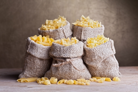raw gold: Pasta assortment in burlap bags on old wooden table