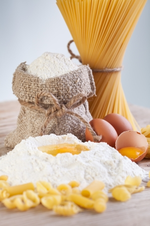 yellow flour: Ingredients for making pasta - flour and eggs on wooden table surface Stock Photo