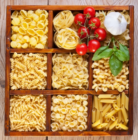 Pasta variety in a compartmented box with garlic, tomatoes and basil photo