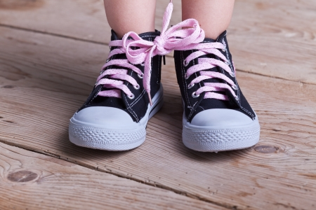 tying: Partial success - child feet with two shoes tied together on wooden floor Stock Photo