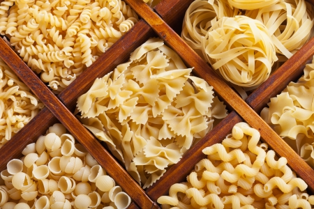 Assorted pasta in wooden compartments - italian food variety