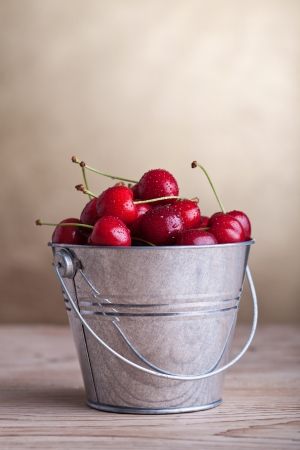 Fresh cherries with waterdrops in a bucket on old table - copyspace