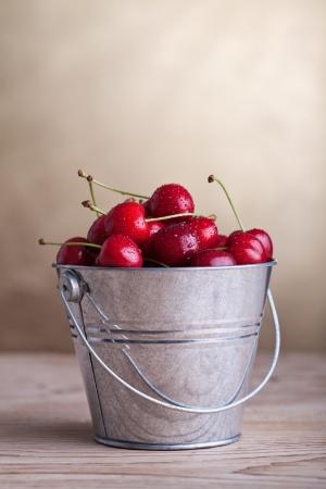 Verse kersen met waterdruppels in een emmer op oude tafel - copyspace