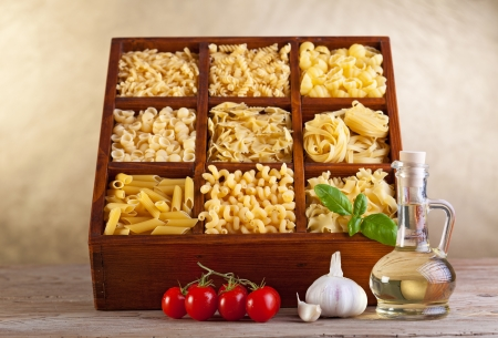 Assorted pasta mix in wooden box and seasoning ingredients photo
