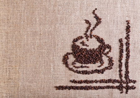 Coffee cup made of beans on burlap - with copy space photo