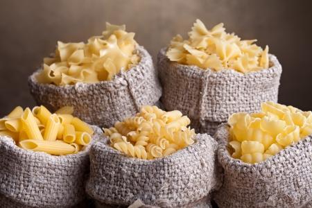 Traditional pasta assortment in burlap bags - closeup