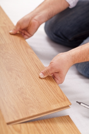 Laying laminate flooring, fitting the next piece - closeup photo