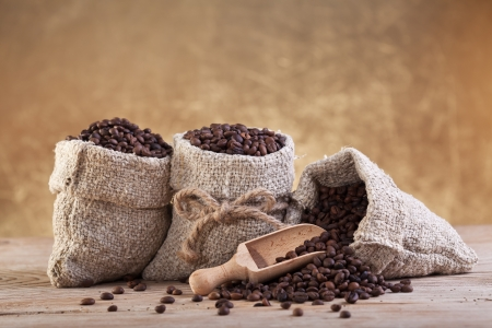 Roasted coffee beans in burlap bags on old wooden table photo
