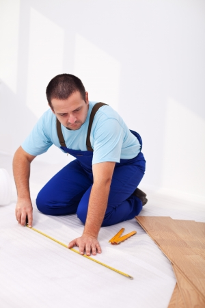 Man in jump suit laying laminate flooring - measuring and thinking Stock Photo - 14448195