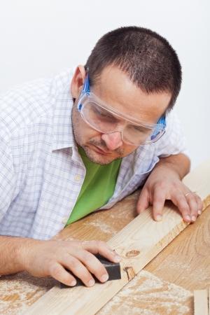 planck: Man polishing wooden planck by hand with sandpaper