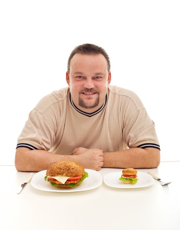 eating right: Size matters in your diet - overweight man pondering how much to eat Stock Photo