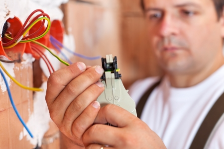 Electrician installing electric wires in a new building - closeup on hands photo