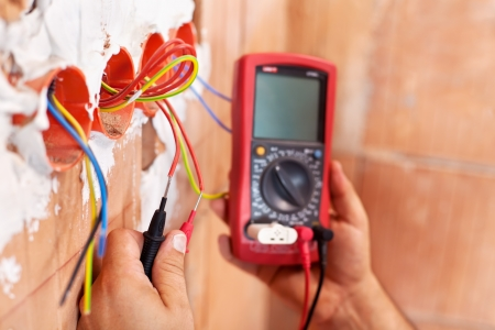 wire: Electrician working with measuring instrument and wires - closeup on hands
