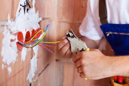 alicates: Manos con alicates de electricista y un mont�n de cables Foto de archivo