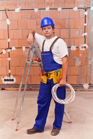 Elektricien op het werk site in een nieuw gebouw te installeren kabels Stockfoto