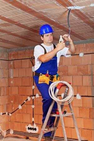 Elektricien gewerkt aan het plafond draden staande op ladder