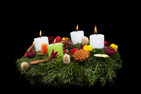 Traditional advent wreath with natural decorations -  isolated on black photo