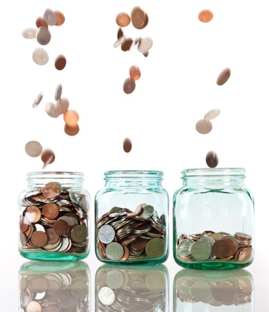 money jar: Savings rate concept - jars in row filling up with falling coins, focus on middle jar