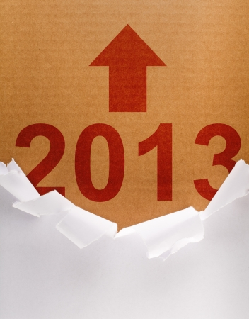 Torn wrapping paper revealing brown cardboard box with the new year Stock Photo - 16101793