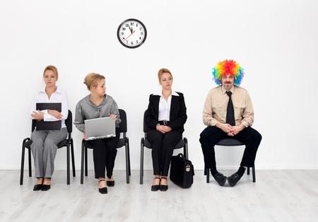 Er is een op de menigte - clown onder sollicitanten wachten Stockfoto