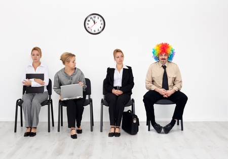 Theres one in every crowd - clown among job candidates waiting photo