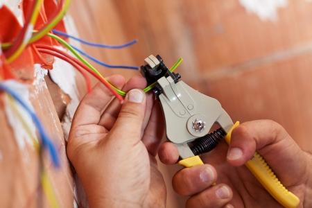 Elektricien afpellen isolatie van de draden - close-up op handen en tangen