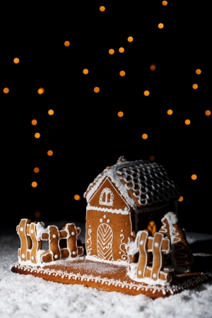 Gingerbread house in the snow under starry sky - christmas setting with copy space photo